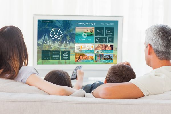 Family sitting on sofa watching television together at home